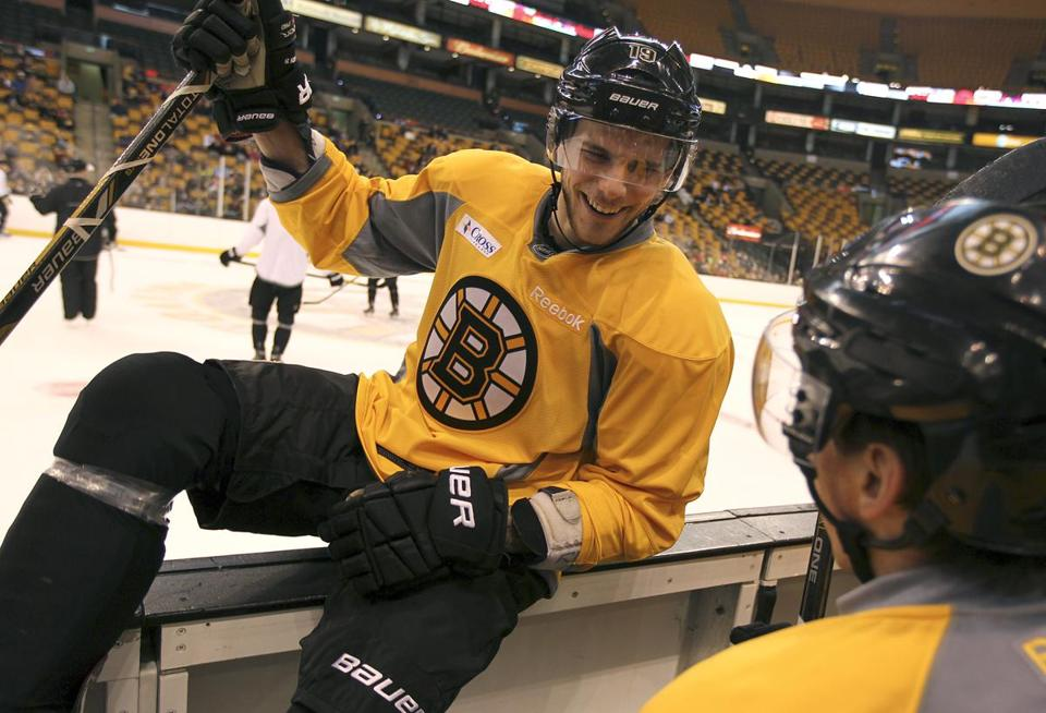 Tyler Seguin has a smile for linemate Brad Marchand as he hops over the boards at Bruins practice.