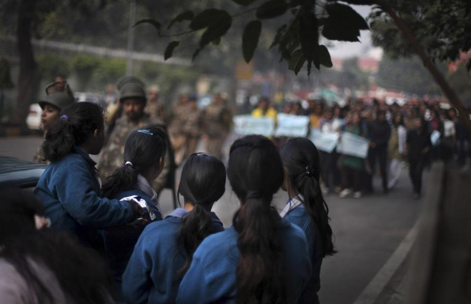 A group of school girls watched as antirape protesters demonstrated in New Delhi in December.