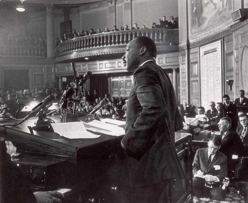 "April 22, 1965:  The Rev. Martin Luther King  Jr. told a joint session of the Massachusetts Legislature that segregation must die if America and democracy are to live. Spectators stood in the packed gallery and some legislators used camp stools on the crowded House floor. King said he came to the Bay State not to condemn but to encourage. He traced the birth of liberty here and warned ""that from these halls liberty must be preserved."""