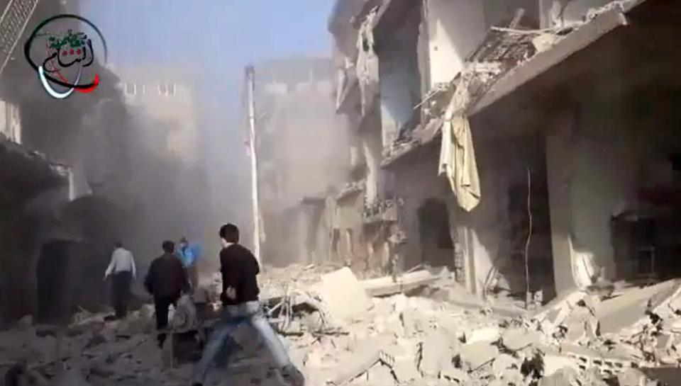 Syrian men ran to aid injured people in the aftermath of a strike by Syrian government warplanes on the residential neighborhood of Maadamiyeh south of Damascus Monday.