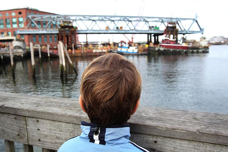 Seven-year-old William Gear of York, Maine, was among about 100 onlookers who gathered to watch the first of three spans of the replacement Memorial Bridge installed on the Piscataqua River on Tuesday morning.