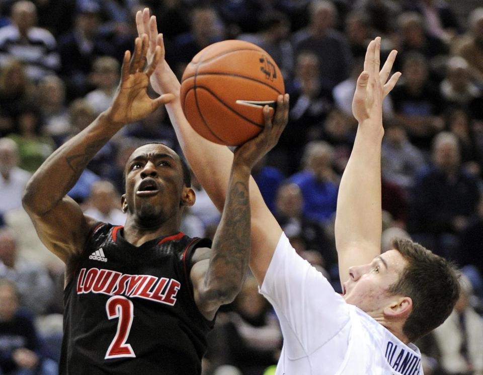 Louisville's Russ Smith drives by UConn's Tyler Olander for 2 of his game-high 23 points in a Cardinals victory.