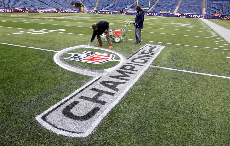 Patriots grounds crew-member Jim Kelly works on the championship-game logo on the Gillette Stadium turf in anticipation of Sunday's game.