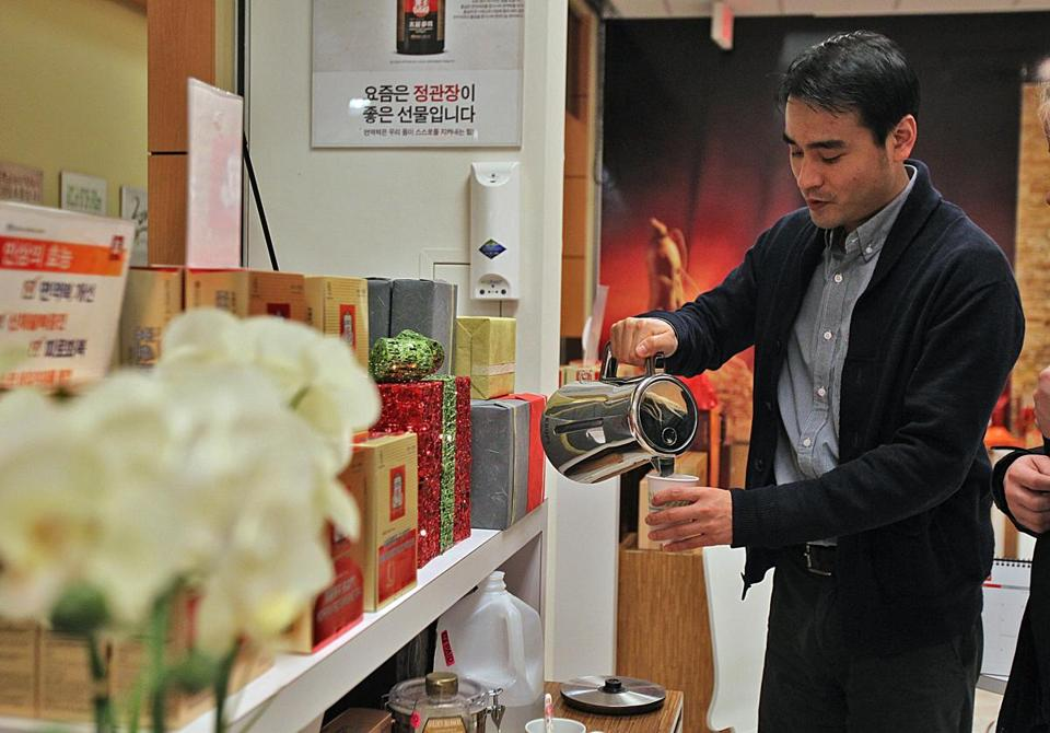 Owner Jaeho Jung pours tea for a customer at KGC Ginseng Co. at the H Mart in Burlington.
