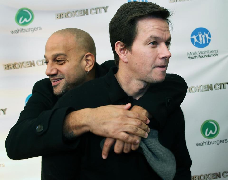 "Director Allen Hughes (left) gives Mark Wahlberg a hug at the ""Broken City"" premiere Tuesday night."