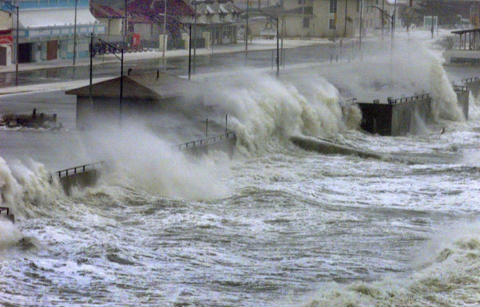Waves crash over the seawall at Nantasket Beach in Hull during a storm-driven high tide.