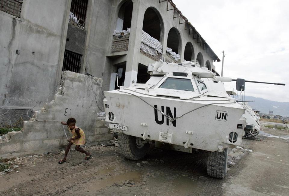 A girl played near a UN armored vehicle belonging to Jordanian peacekeepers at slum in Port-au-Prince, Haiti.