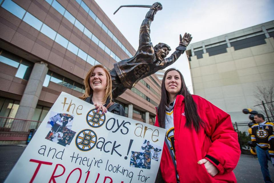 "Kassie LaPointe and Brittany McMakin held a sign in front of Bobby Orr's statue outside TD Garden in Boston before the game. ""It's about time,"" LaPointe said. ""Hockey's back."""