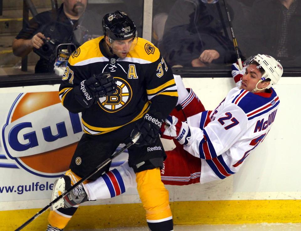 Patrice Bergeron of the Bruins delivers a bone-crunching check to the Rangers' Ryan McDonagh in the first period.