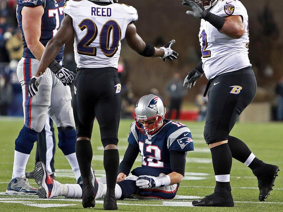 The Ravens celebrated after stopping Patriots quarterback Tom Brady on a critical fourth-down play late in Sunday's contest.