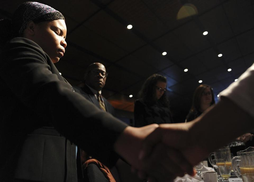 Roudna Joseph joined hands with colleagues during the final benediction at the annual Martin Luther King Jr. memorial breakfast at the Boston Convention and Exhibition Center Monday.