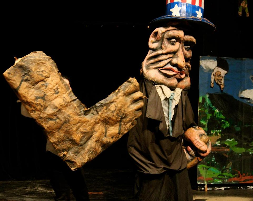 "In ""The Possibilitarians,"" a giant papier-mâché figure towers over cast members of Bread and Puppet Theater."