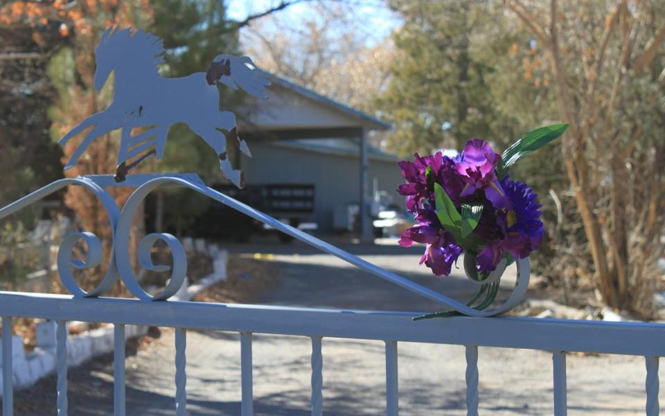 Flowers were placed at the entrance to a home where a couple and their three young children were found shot to death south of Albuquerque.