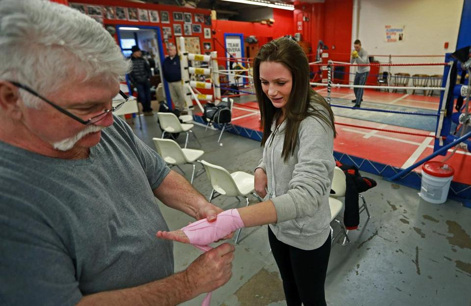Norman Stone of the Somerville Boxing Club helped Kourtney Yurko wrap her hand before her workout.