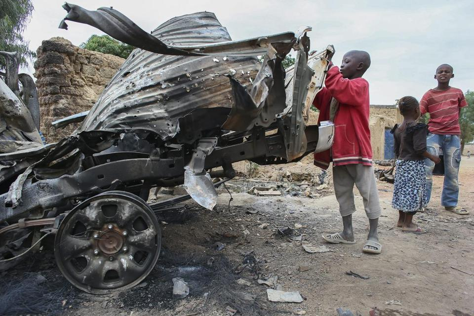Residents viewed damage to rebel vehicles on Friday after French airstrikes in recently liberated Diabaly, Mali.