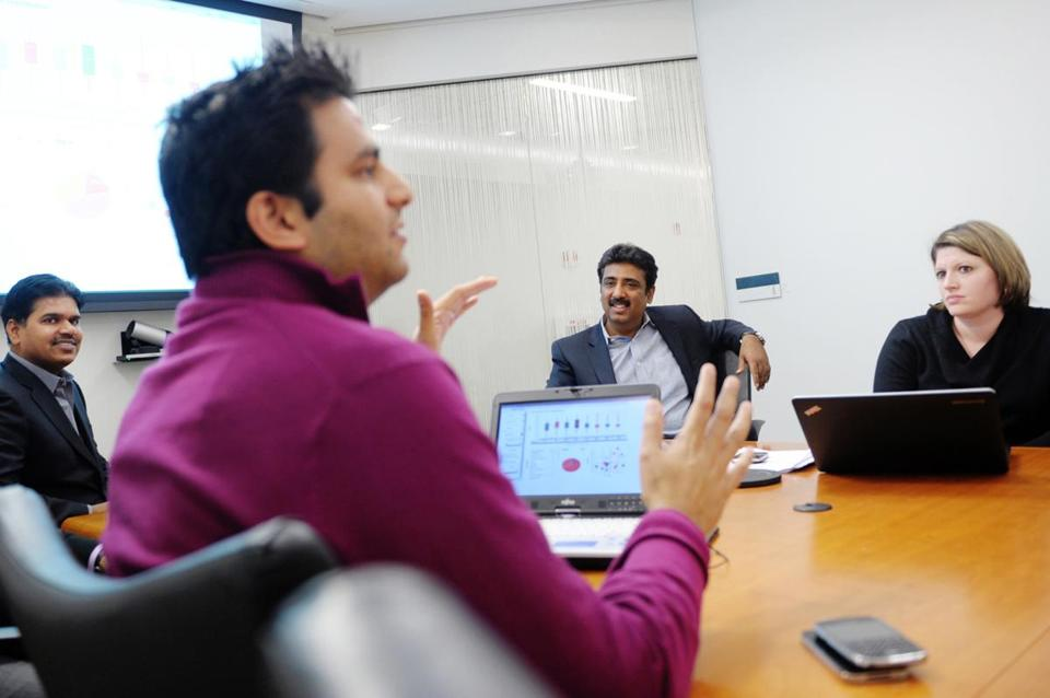 Girish Navani, CEO of eClinicalWorks (center) listened to Rohan D'Souza speak while Dr. Raj Dharampuriya (left) and Laura Bujnowki looked on during a Jan. 25 meeting in Westborough.