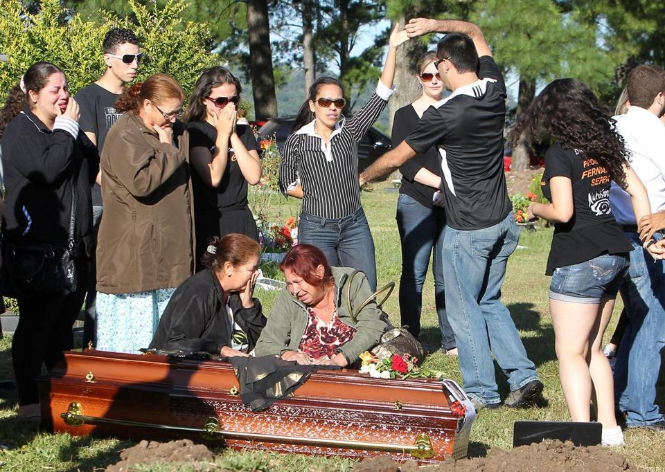 Relatives and friends mourn fire victim Tanise Cielo at a cemetery in Brazil.