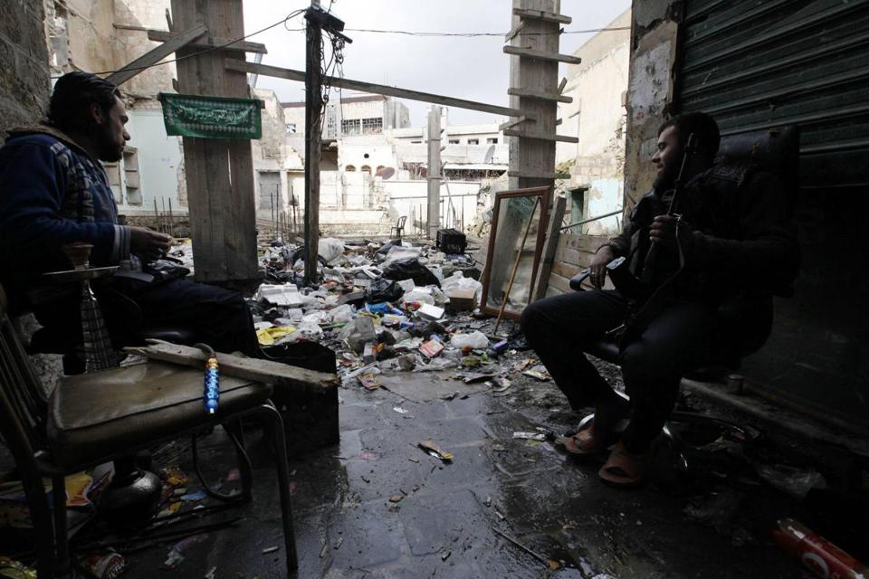 A Free Syrian Army fighter sat next to a water pipe and looked towards a mirror to monitor forces loyal to Syria's President Bashar al-Assad in old Aleppo, January 29, 2013.