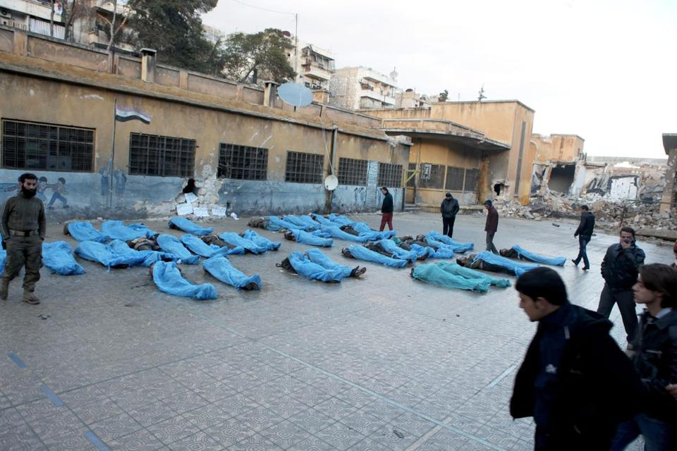 Bodies in blue plastic bags lay in an Aleppo school courtyard while residents tried to identify missing relatives. At least 50 bodies were found but the toll could be twice that.
