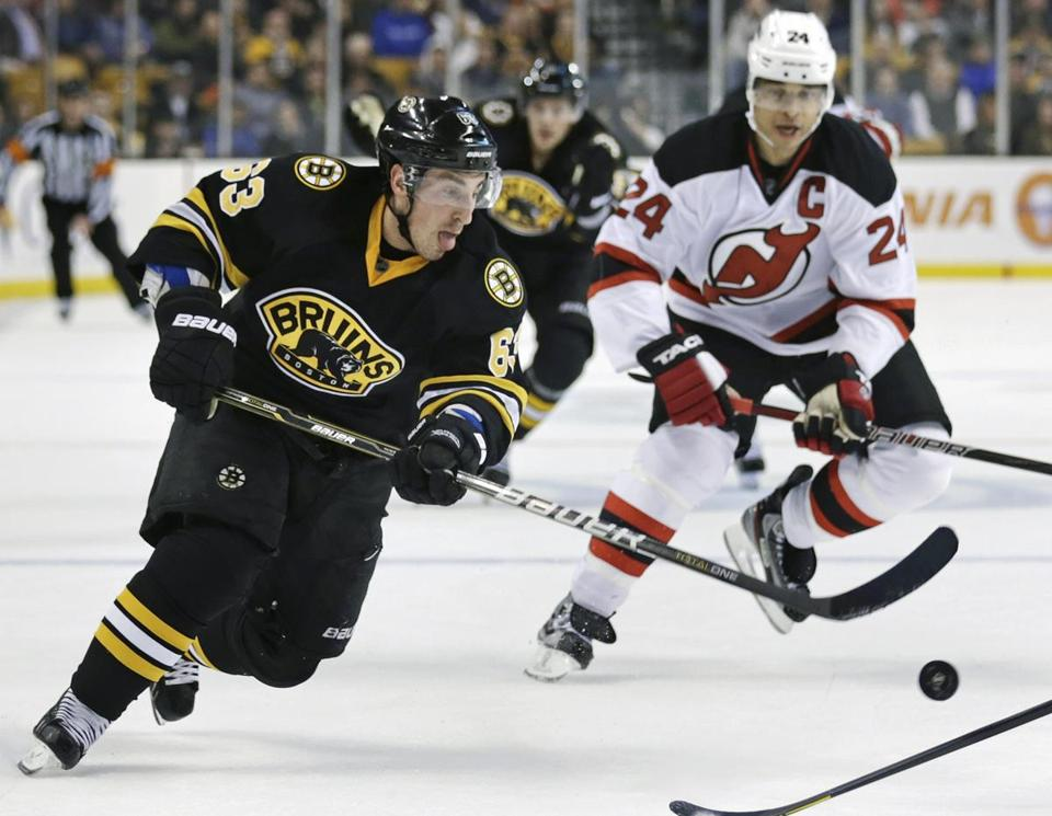 Boston Bruins left wing Brad Marchand controled the puck against New Jersey Devils defenseman Bryce Salvador during the second period of an NHL hockey game in Boston, Tuesday, Jan. 29, 2013.
