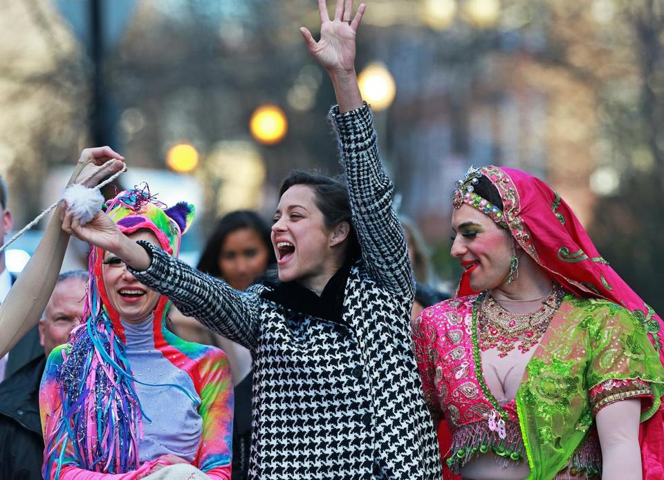 Actress Marion Cotillard (with Renee Rober, left, and Ben Moss) waves during the Hasty Pudding parade.