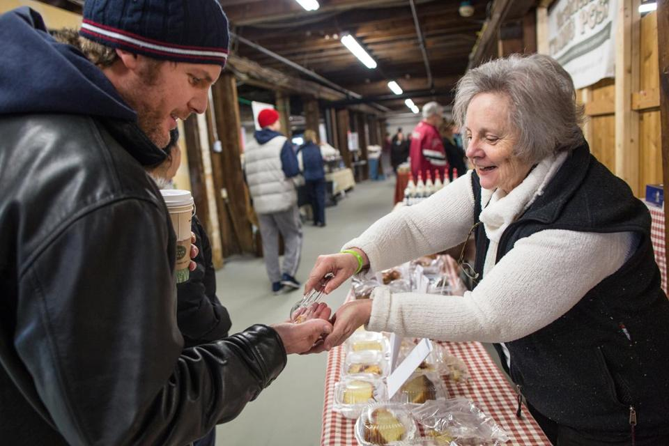 Jonathan Bluestein of Raynham gets a sample from Linda Spartichino, who operates Homemade Heaven Bakery at the Easton Winter Farmers Market.