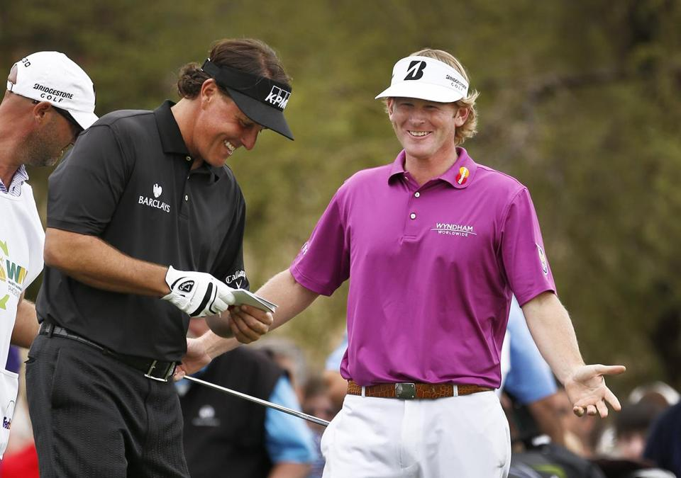 Phil Mickelson, left, and Brandt Snedeker laughed about Mickelson's long birdie putt on the seventh hole during the final round of the Waste Management Phoenix Open golf tournament on Sunday in Scottsdale, Ariz.
