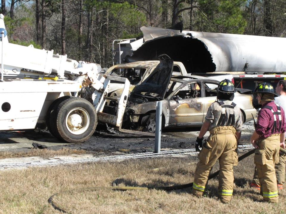 A forklift moved a burned car near Montrose, Ga., where more than two dozen cars, trucks, and tractor-trailers collided.
