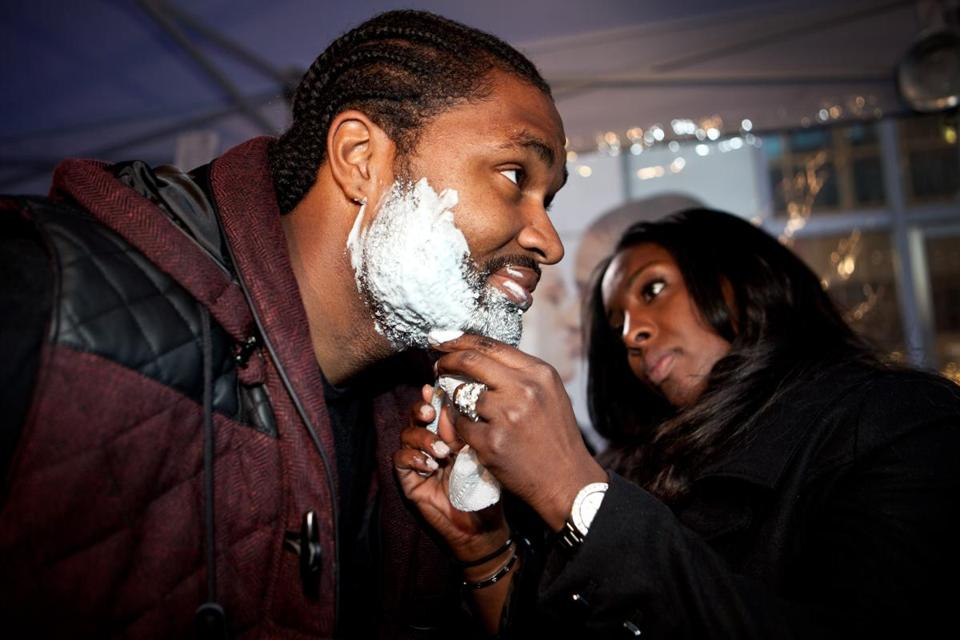 New England Patriot Jerod Mayo gets a shave from his wife, Chantel, at the Prudential Center.