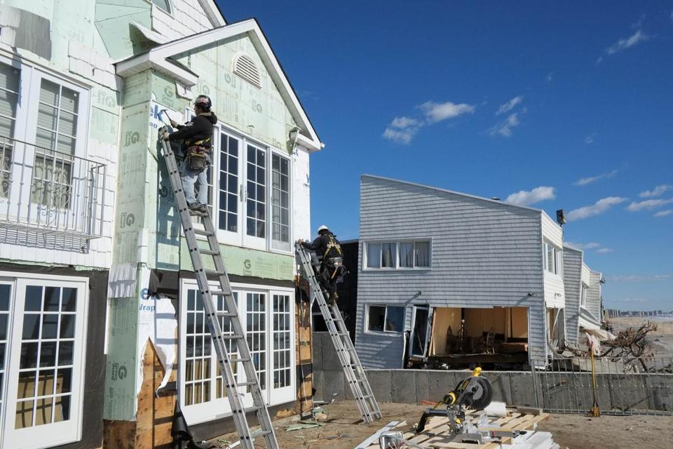 Carpenters installed new siding on a storm-damaged beach house in January in Far Rockaway, N.Y. Much of the first round of federal aid is planned to go to loans and grants to affected homeowners and businesses.