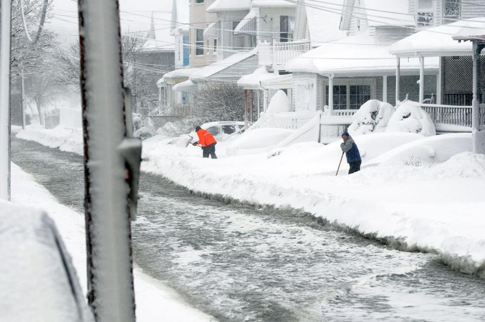 Residents shoveled snow as flood waters flowed down Coral Street in Winthrop.
