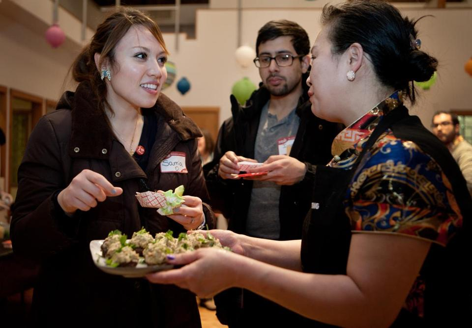 Patty Chen (right), chef at Patty's Kitchen and All Asia, serves small plate samples to (from left) Samia Osman and Imran Ghare at the Kitchensurfing Yelp party.