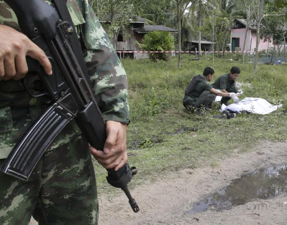 Thai soldiers inspected the body of one of the slain insurgents after the attack on the base. Authorities also confiscated 13 rifles, three pistols, and a pickup truck.