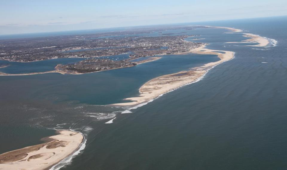 An aerial view shows the breach in a thin strip of barrier beach off southeastern Cape Cod. Chatham is in the background.