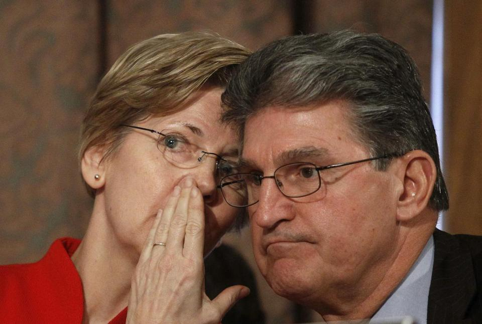 Senator Elizabeth Warren conferred with Democratic colleague Joe Manchin of West Virginia during testimony at the Senate Banking Committee on Thursday.