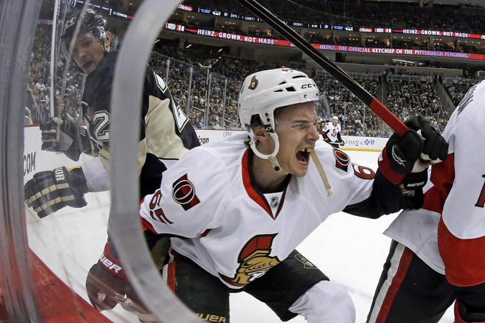 Ottawa Senators defenseman Erik Karlsson grimaced as he fell to the ice after colliding with Pittsburgh Penguins left wing Matt Cooke, left, during the second period of an NHL hockey game in Pittsburgh Wednesday, Feb. 13, 2013.