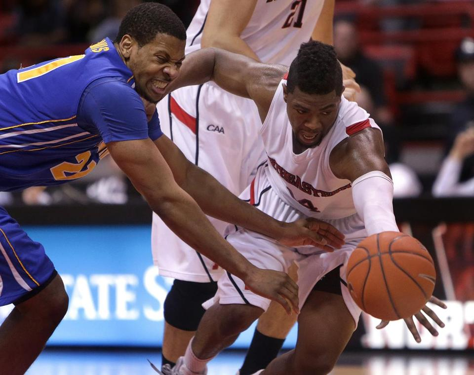 NU's Jonathan Lee is fouled by Delaware's Marvin King-Davis while driving to the basket during the first half.