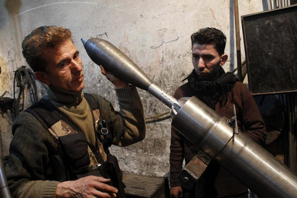 A Free Syrian Army fighter held an improvised mortar shell inside a factory that previously manufactured steel and iron in Aleppo.