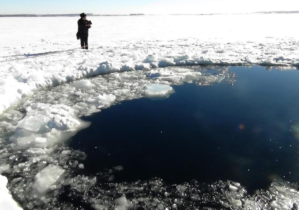 Divers searched under a 20-foot hole in the ice of a lake but found no large pieces of the meteor in Russia.