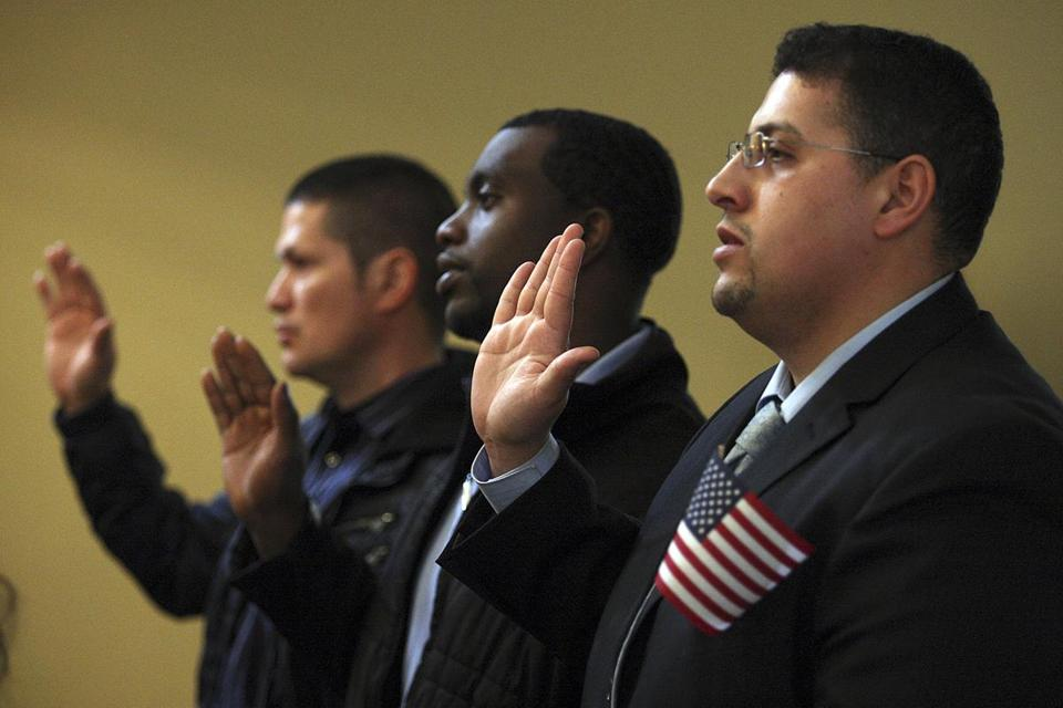 Younes Mekrami of Revere (right) was one of those who took the oath of citizenship Wednesday in Boston.