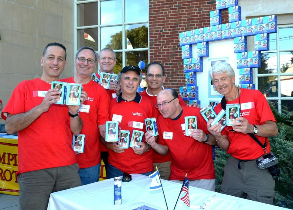 Temple Emanuel Brotherhood members distribute customized Jewish National Fund collection boxes to children at the temple's annual Kickoff Barbecue in September 2012. Pictured, from left to right, are Roots in Israel Committee members Danny Mandeau, David Beckman (the current Brotherhood president), Bruce Gold, Dennis Buchenholz, Rob Finkel, Peter Matusow, and David Greenfield.