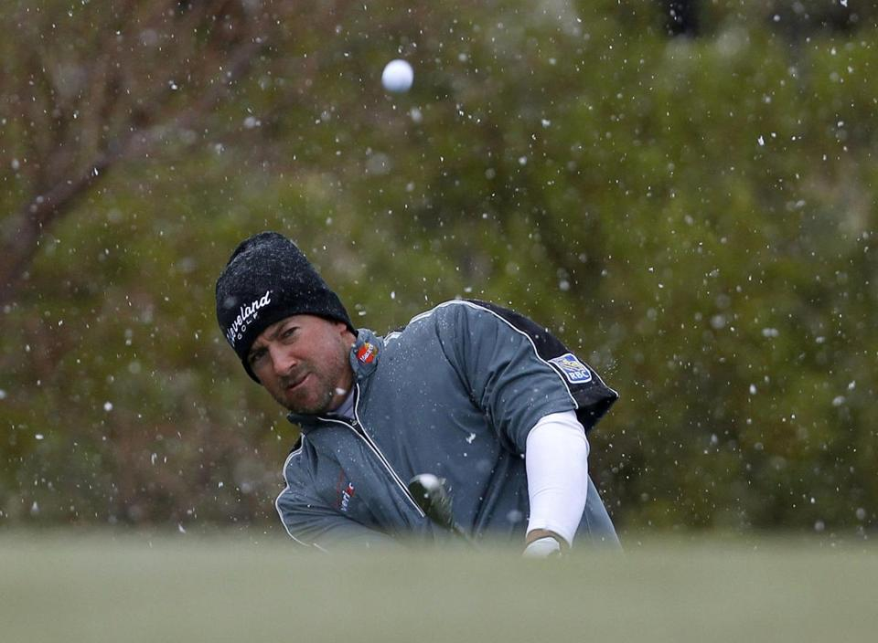 Snow fell as Graeme McDowell chipped onto the first green on Wednesday.
