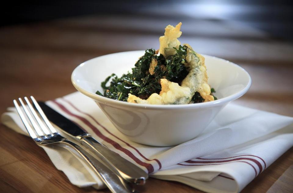 A kale salad with fried parsnips, sunflower seeds, and raisins, garnished with tempura kale chips.