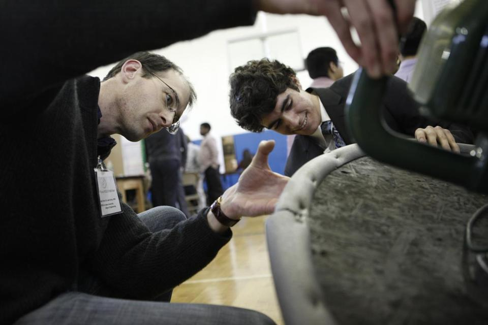 A judge inspects the bottom of a student 's hovercraft during a science fair at the Pioneer Charter School.