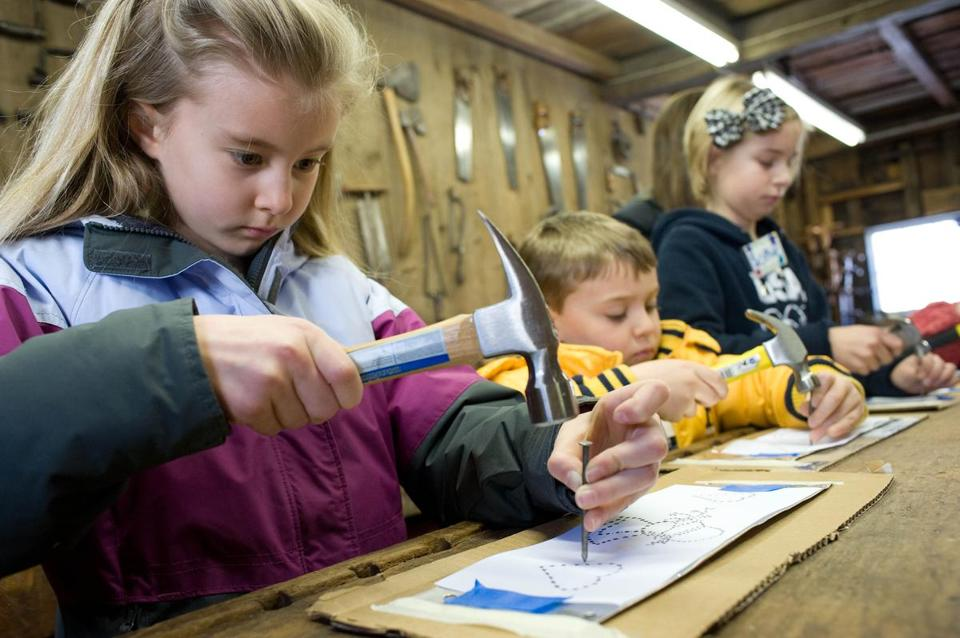 Seven-year-old Michelle Walsh (left) and others use a nail and hammer to punch holes in tin to create lanterns.