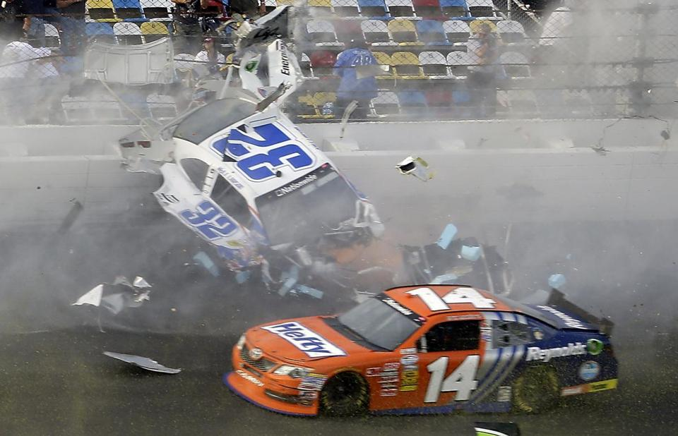 Kyle Larson (32) slides along the wall after hitting the catch fence as Eric McClure (14) goes low after the cars were involved in a multi-car crash on the final lap of the NASCAR Nationwide Series auto race at Daytona International Speedway, Saturday, Feb. 23, 2013, in Daytona Beach, Fla. (AP Photo/John Raoux)