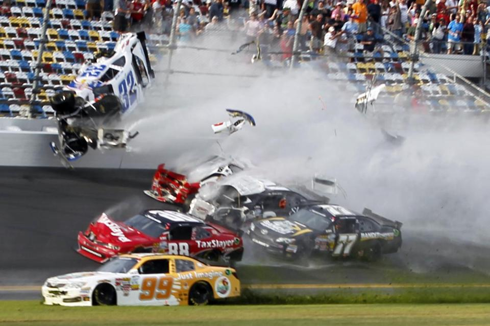 Rookie driver Kyle Larson (32) crashes into the catch fence at the front stretch grandstand at Daytona International Speedway.