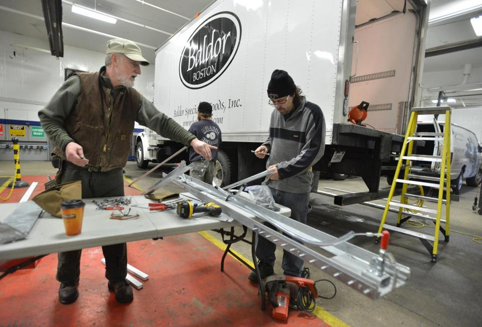 Steve McCoy (left) and Mark Jackson of Brussard Associates work on the frame for sliding curtains in a refrigerated delivery truck in Medford.