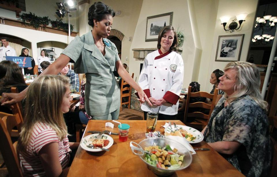 "Michelle Obama had help from chef Julie Elkinton at a ""Let's Move!"" event in a Darden restaurant in Maryland. Jacqueline McElroy, 9, and her mother, Charisse, participated."