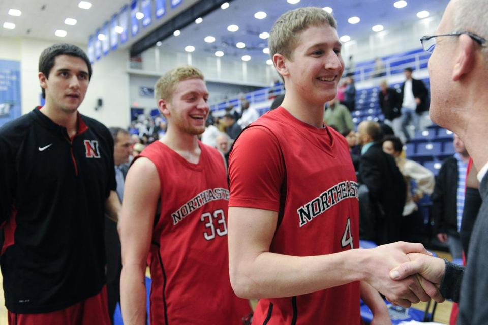 Northeastern's David Walker (4) Zach Stahl (33) are congratulated after clinching the CAA stub.
